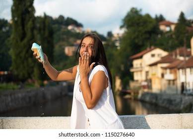 young woman outdoors with dripping ice cream