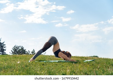 Young woman outdoors on field maintaining healthy lifestyle doing yoga downward-facing dog pose on mat concentrated