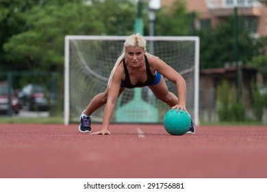 Young Woman Outdoors Performing Push Ups On Medicine Ball Bodybuilding Exercise