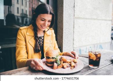 Junge Frau im Freien, die im Restaurant sitzt und Burger - hungrig smilinmg Kaukasierin isst leckeren Hamburger - Hunger, Essen, positives Konzept