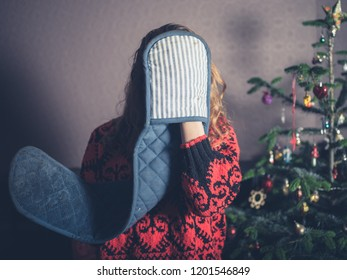 A young woman with oven gloves is standing by the christmas tree