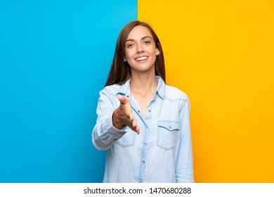 Young woman over colorful background handshaking after good deal