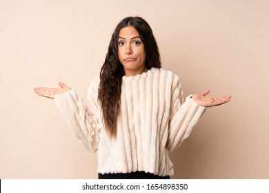 Young woman over isolated background having doubts while raising hands