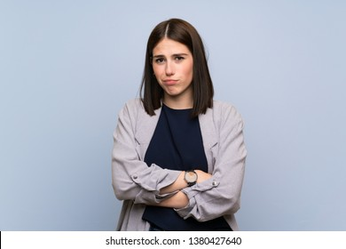 Young woman over isolated blue wall feeling upset