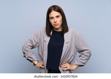 Young woman over isolated blue wall angry