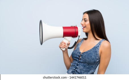 Young woman over isolated blue wall shouting through a megaphone
