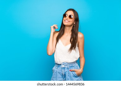 Young woman over isolated blue background with glasses and smiling