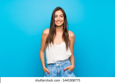 Young woman over isolated blue background laughing