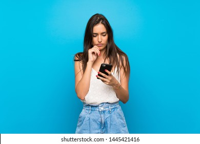 Young woman over isolated blue background thinking and sending a message