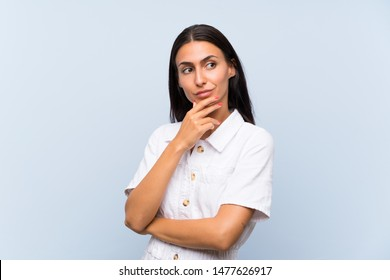 Young woman over isolated blue background thinking an idea