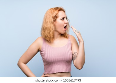 Young woman over isolated blue background yawning and covering wide open mouth with hand