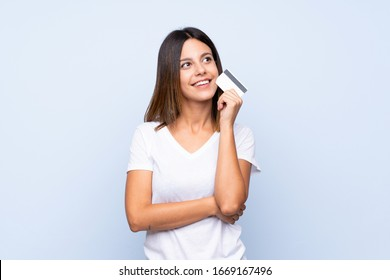 Young woman over isolated blue background holding a credit card
