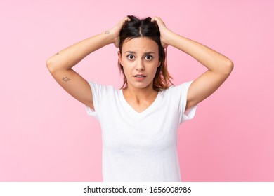 Young woman over isolated pink background frustrated and takes hands on head