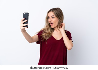 Young woman over isolated white background making a selfie