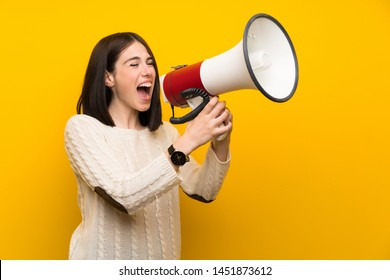 Young woman over isolated yellow wall shouting through a megaphone