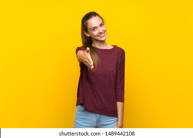 Young woman over isolated yellow background shaking hands for closing a good deal