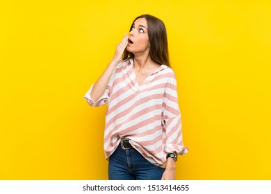 Young woman over isolated yellow background yawning and covering wide open mouth with hand