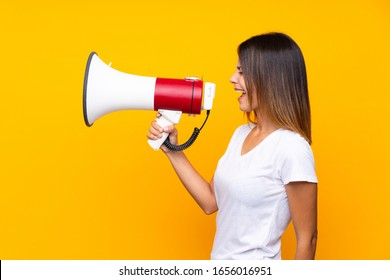 Young woman over isolated yellow background shouting through a megaphone