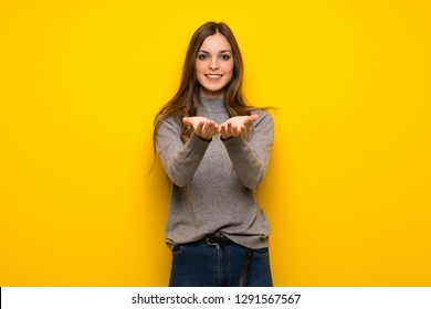 Young woman over yellow wall holding copyspace imaginary on the palm to insert an ad