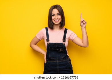 Young woman over yellow wall showing and lifting a finger in sign of the best