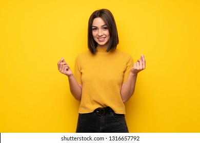 Young woman over yellow wall making money gesture