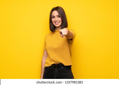 Young woman over yellow wall points finger at you with a confident expression