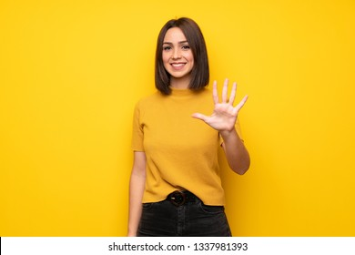 Young woman over yellow wall counting five with fingers