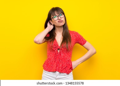 Young woman over yellow wall having doubts