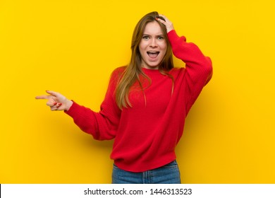 Young woman over yellow wall surprised and pointing finger to the side