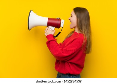 Young woman over yellow wall shouting through a megaphone