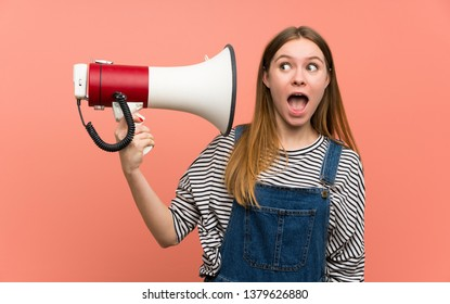 Young woman with overalls over pink wall taking a megaphone that makes a lot of noise