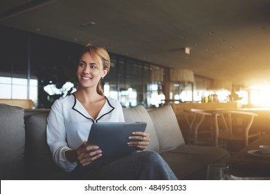 Young woman owner is smiling to client, while is sitting with portable touch pad in her luxury restaurant. Cheerful female manager with digital tablet in hands having breakfast in modern coffee shop