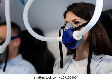 Young woman with oxygen mask during treatment in hyperbaric chamber.