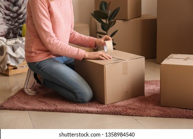 Young woman packing belongings in room