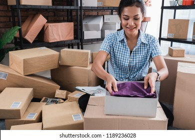 Young woman packing of clothes on the boxes to be shipped in her office