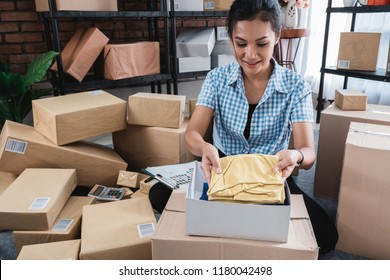 Young woman packing of clothes put on the boxes to be shipped in her office