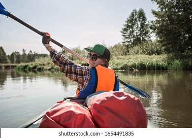 Young woman with a paddle. Back view. Girl rowing an oar during kayaking. A boat loaded with stuff. Relocation to another place by boat. Family active weekend.