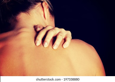 Young woman with pain in her back. Isolated on white background.
