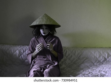 Young woman with painted face like scary clown or joker wearing japanese/chinese hat. Halloween costume.