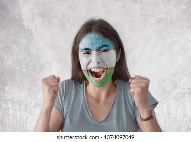 Young woman with painted flag of Uzbekistan and open mouth looking energetic with fists up