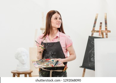A young woman painter in a bright white studio draws a picture on canvas on an easel. Pink checked shirt, black apron, on the background of the pattern and tools.