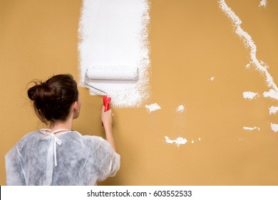 young woman painting a brown wall in white color, renovation and improvement