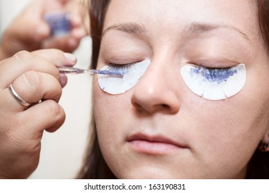 Young woman painting with a brush his eyelashes. Permanent staining