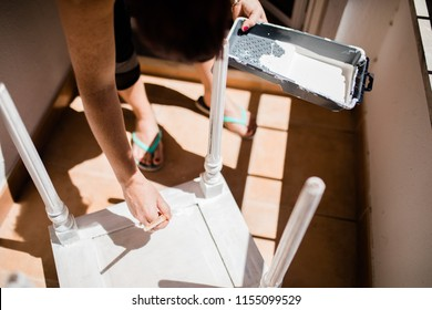 Young woman painting furniture and remodelling