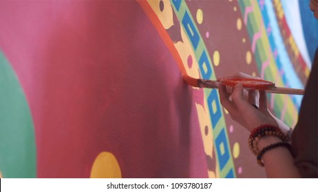 Young woman painting graffiti or mural on wall with brush, close-up. Clip. Painter performing street art. Close-up on hands of a painter with a brush in acrylic paint