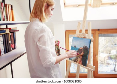 Young woman painting at home. Room with white walls and book shelves on a background