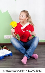 Young woman painting interior wall of home