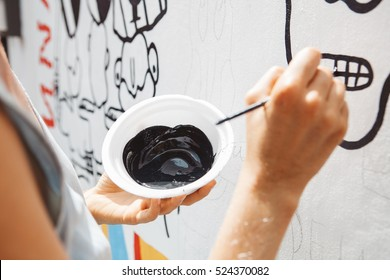Young woman painting a picture on the wall, street artist, brush in hand and black paint
