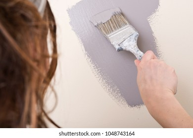 Young woman is painting wall with brush in bathroom under remodeling