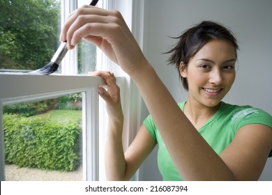Young woman painting window frame, smiling, portrait, close-up